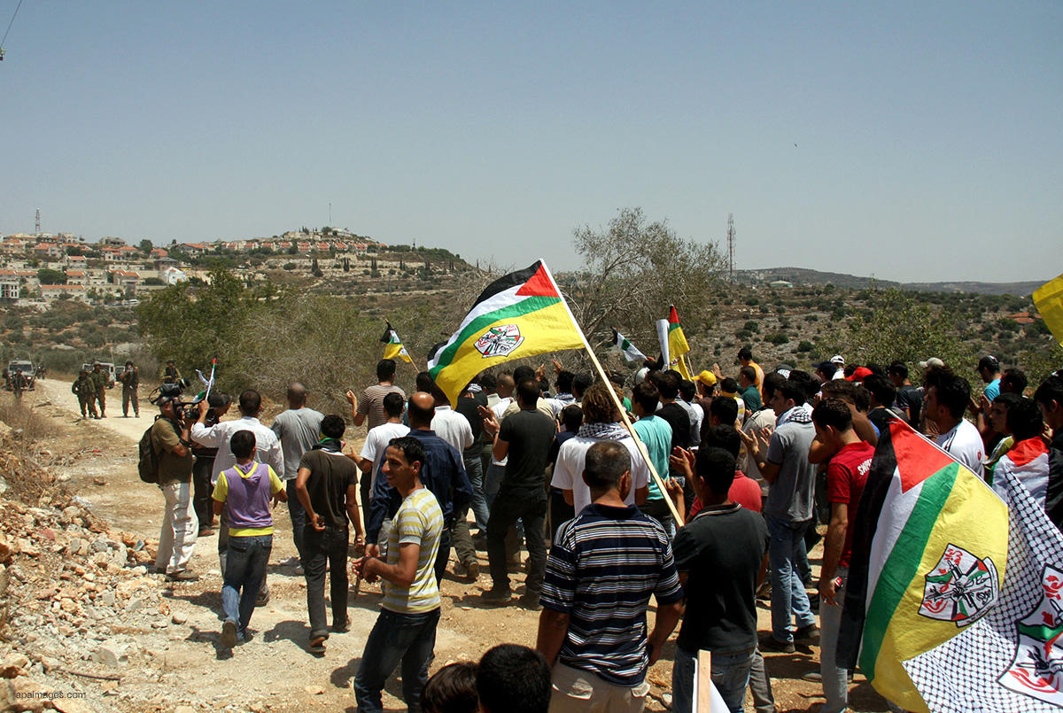 Palestinian protestors take part in a demonstration againsty Israeli soldiers during the Second Intifada, on July 22, 2011 in the West Bank village of Kfar Kadum