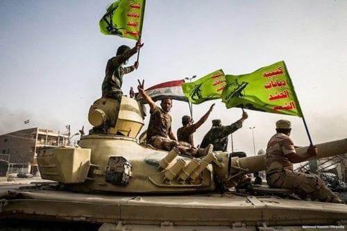 Image of militants raising the Iraq and Popular Mobilisation Forces (PMF) flag [Mahmoud Hosseini/Wikipedia]
