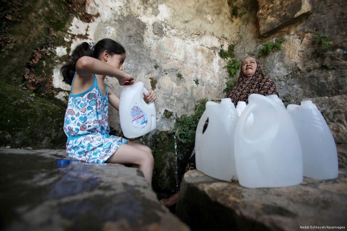A Palestinian girl fills up bottles with spring water in West Bank, Israel [Nedal Eshtayah/Apaimages]