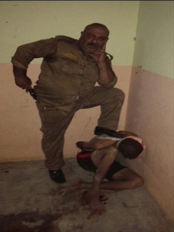 Image of an Iraqi Christian militia leader violently stepping on a Iraqi youth