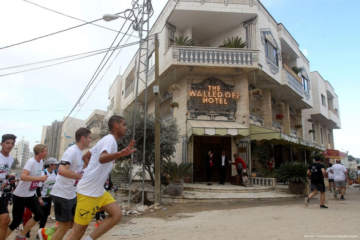 Participants run past the the Walled-Off Hotel, Banksy's newly opened hotel in Bethlehem, West Bank [Wisam Hashlamoun/Apaimages]