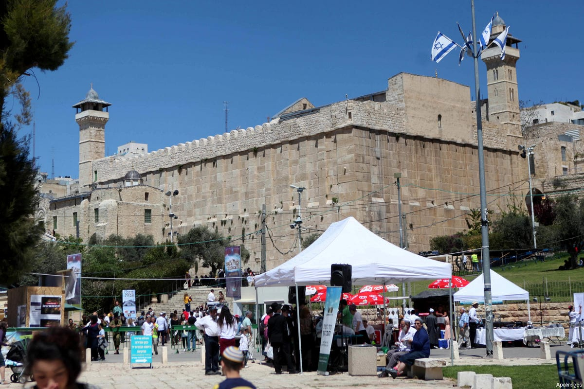Israelis walk outside the Ibrahimi Mosque, also called the Tomb of the Patriarchs, during the Jewish Passover holiday, in the West Bank city of Hebron, April 5, 2015 [Mamoun Wazwaz / ApaImages]