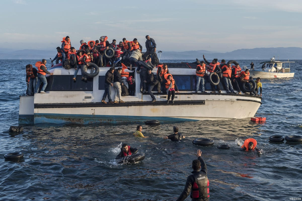 """Syrian and Iraqi refugees arrive from Turkey to Skala Sykamias, Lesbos island, Greece on 30 October 2015. Spanish volunteers (life rescue team - with yellow-red clothes) from """"Proactiva open arms"""" help the refugees [Ggia / Wikipedia]"""