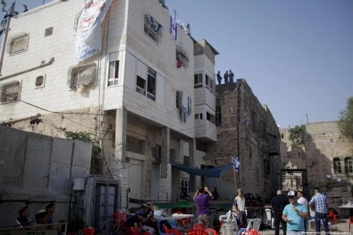An Israeli flag can be seen atop a Palestinian home in the occupied West Bank city of Hebron on 26 July 2017. Over 100 settlers stormed the house and evicted the Palestinian family which legally owns it. [Mamoun Wazwaz /Anadolu Agency]