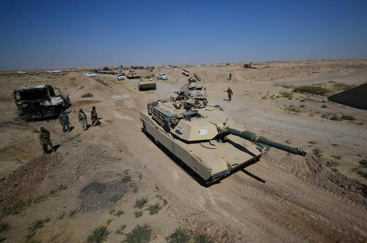 A tank of Iraqi army members and Shia Popular Mobilization Forces (PMF) are seen in Al-Al-Fateha military airport south of Hawija, Iraq, October 2, 2017 [Stringer / Reuters]