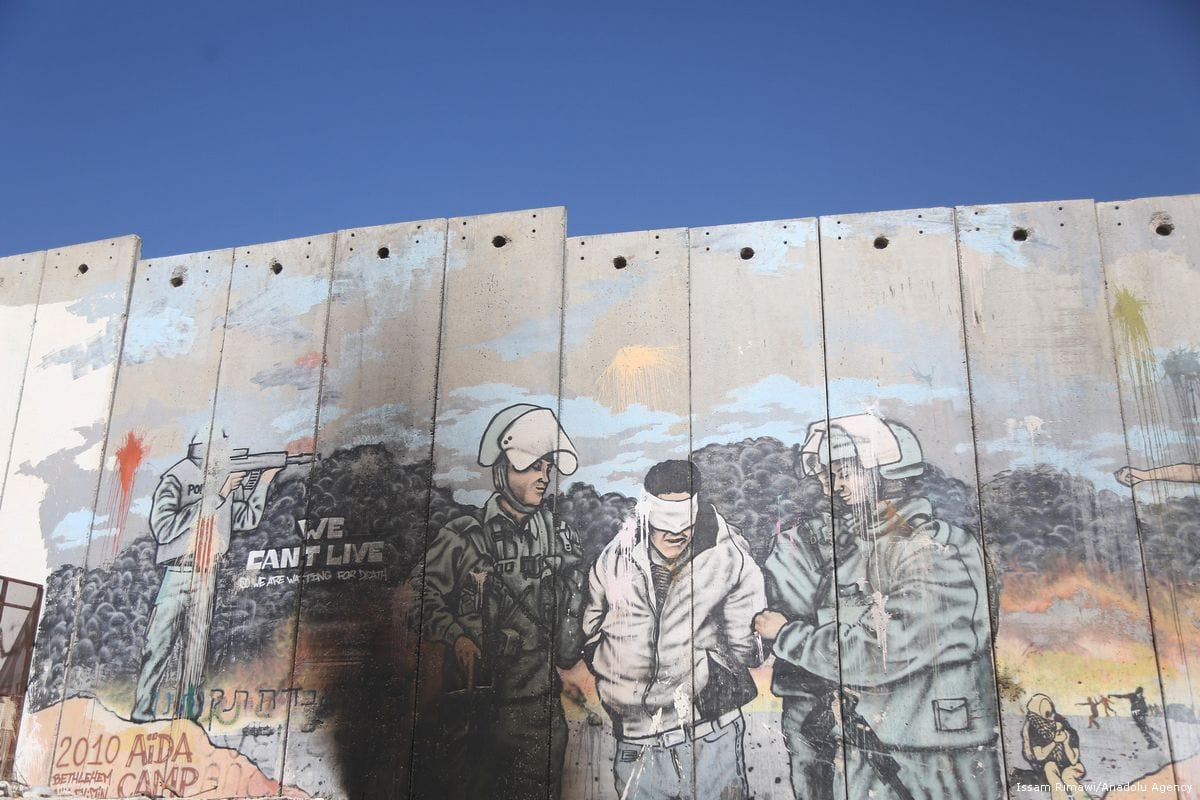 Graffiti art is seen on the illegal Israeli Separation Wall in the occupied West Bank town of Bethlehem on 1 November 2017 [Issam Rimawi/Anadolu Agency]