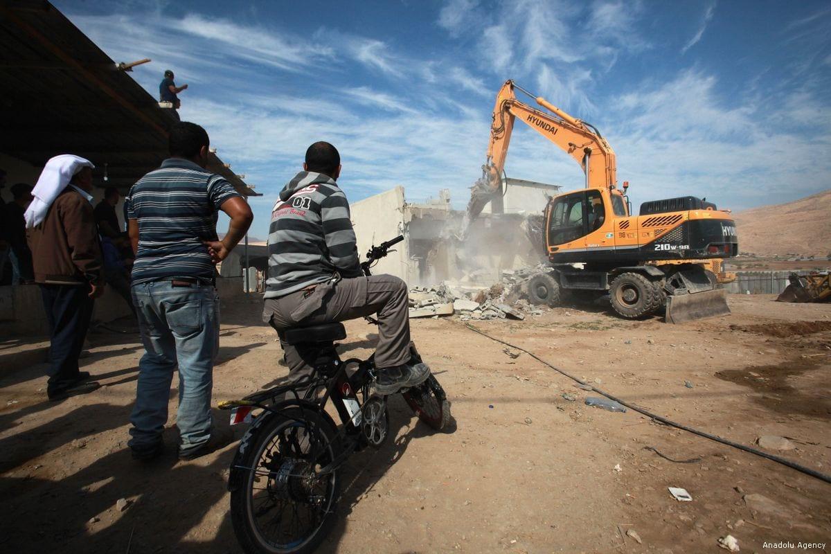 Palestinians watch the demolition of their home in Jordan Valley on 7 November 2017 [Nedal Eshtayah/Anadolu Agency]