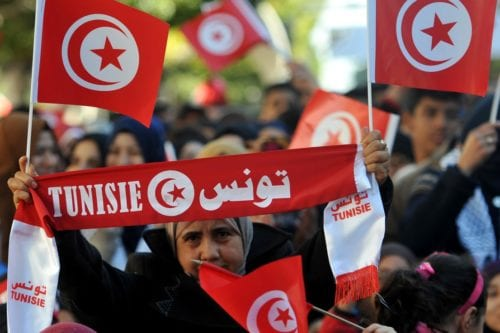 A woman holds her national flag during a rally on 14 January 2016 in the Habib Bourguiba Avenue in the capital Tunis to mark the fifth anniversary of the 2011 revolution. [FETHI BELAID/AFP/Getty Images]
