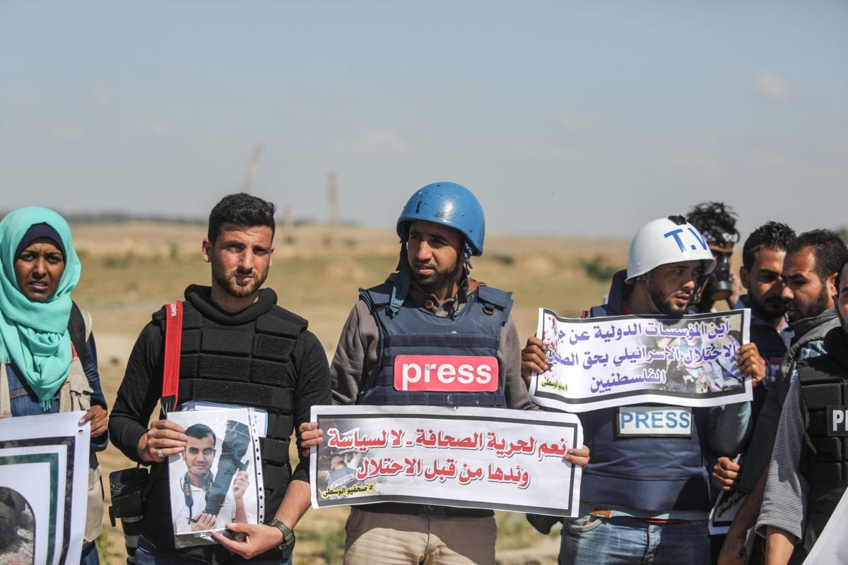 """Palestinian journalists hold placards to commemorate their Palestinian colleague Yasir Murteca, who was martyred by Israeli soldiers during """"Great March of Return"""" near Gaza-Israel border, during a protest in Gaza City, Gaza on 9 April, 2018 [Ali Jadallah/Anadolu Agency]"""