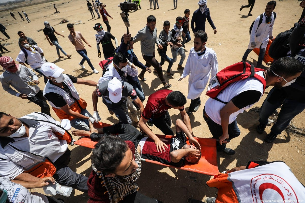 """A wounded Palestinian demonstrator is carried by health team members after getting injured on intervention of Israeli occupation forces during a demonstration within the """"Great March of Return"""" in Khan Yunis, Gaza on 11 May 2018. [Mustafa Hassona/Anadolu Agency]"""