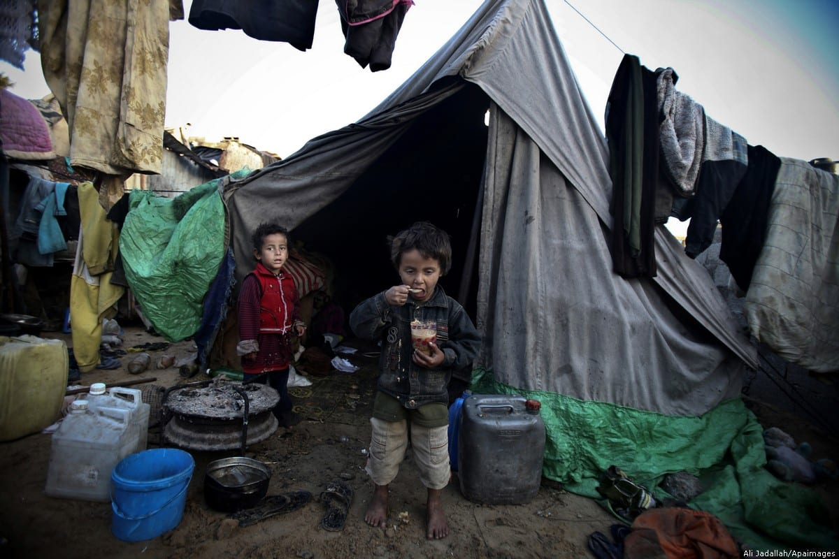 Palestinian children are seen outside their makeshift tent in Gaza [Ali Jadallah/Apaimages]