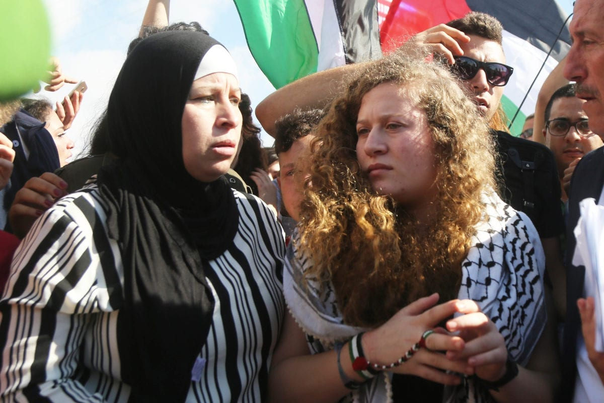 """Palestinian teenager Ahed al-Tamimi (C), who was awarded the """"Hanzala Award for Courage"""" in Turkey, is released with her mother Nariman Tamimi (not seen) after 7 months in prison at Israeli check point in Nabi Saleh district of Ramallah, West Bank on 29 July, 2018 [Issam Rimawi/Anadolu Agency]"""