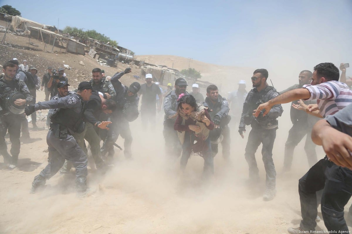 Israeli forces can be seen violently attacking Palestinians as they evict them from their homes in Khan Al-Ahmar village of Jerusalem on 4 July 2018 [Issam Rimawi/Anadolu Agency]