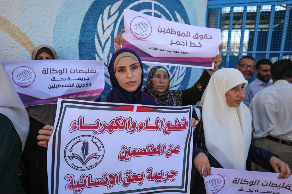 The United Nations Relief and Works Agency for Palestine Refugees in the Near East (UNRWA) staff stage a protest against the agency's decision to scale down its operations and lay off some of its staff in front of the UNRWA's office in Gaza City, Gaza on 6 August, 2018 [Mustafa Hassona/Anadolu Agency]