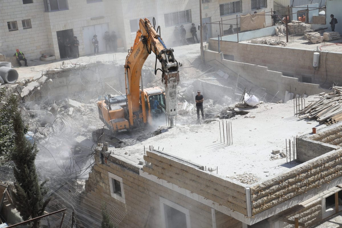 Israeli excavators demolish a Palestinian building for allegedly being unauthorized in Al-Issawiya district of East Jerusalem on August 15, 2018. [Mostafa Alkharouf/Anadolu Agency]