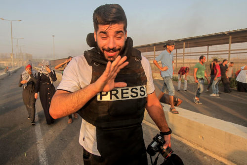 Palestinian journalist and Palestinian protesters gather during clashes with Israeli troops following a protest against the United States decision to stop funding and backing the United Nations agency for Palestinian refugees (UNRWA) at the Erez crossing with Israel in the northern Gaza Strip on 4 September, 2018 [Dawoud Abo Alkas/Apaimages]