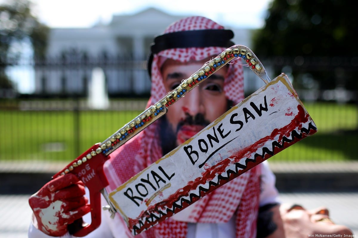 Protestor dresses in Bin Salman mask and brandishes a bloodied saw in Washington DC on 2 October 2018 [Win McNamee/Getty Images]