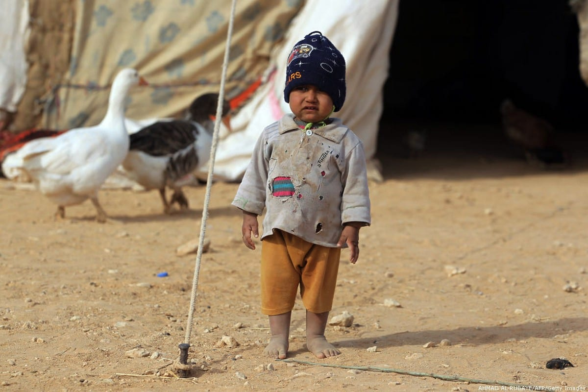 An Iraqi child, displaced from the city of al-Qaim, stands outside a tent near al-Qaim, in western Anbar province, on the Syrian border on November 2, 2017. [AHMAD AL-RUBAYE/AFP/Getty Images]