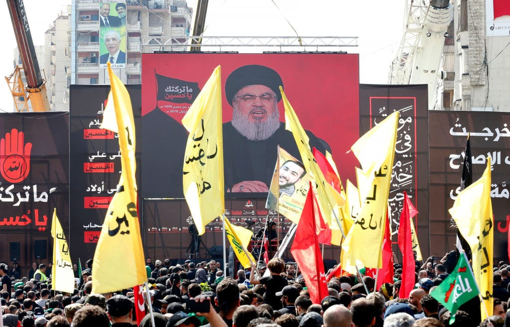 Supporters of Lebanon's Shia movement Hezbollah gather near a giant poster of their leader Hassan Nasrallah during a ceremony to mark Ashura on 20 September 2018 in Beirut [Anwar Amro/AFP/Getty Images]
