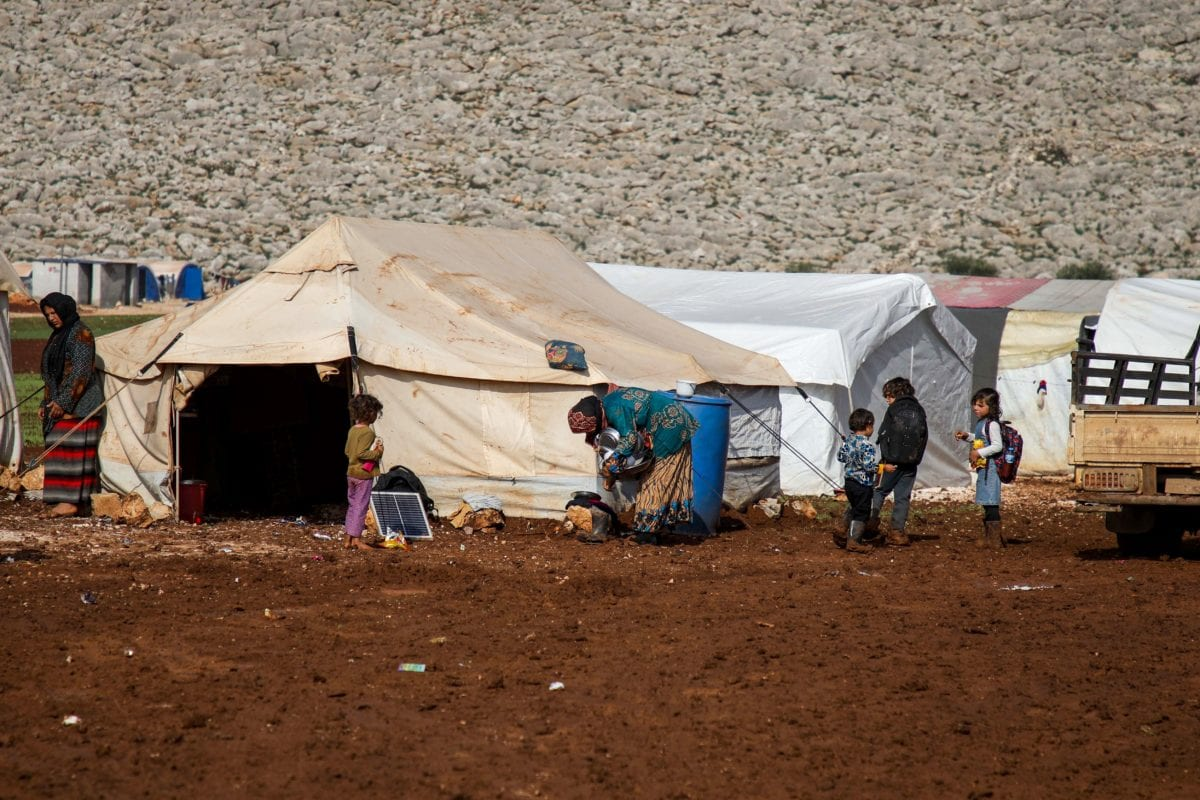 This picture taken on shows A general view of Syrians outside tents at a camp for the displaced near the town of Sarmada in the northern countryside of the rebel-held Idlib province, on December 1, 2018 (Photo by AAREF WATAD/AFP/Getty Images)