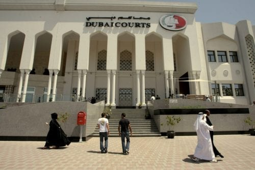 Pedestrians walk past Dubai's courts building during a hearing on 4 April 2010 [AFP/Getty Images]