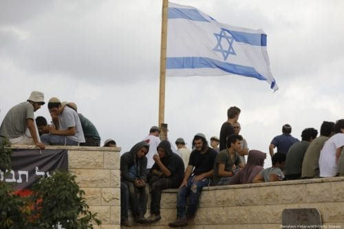 Israeli settlers gather next to their flag on a rooftop of a house in Bethlehem, in the occupied West Bank on 12 June 2018 [Menahem Kahana/AFP/Getty Images]
