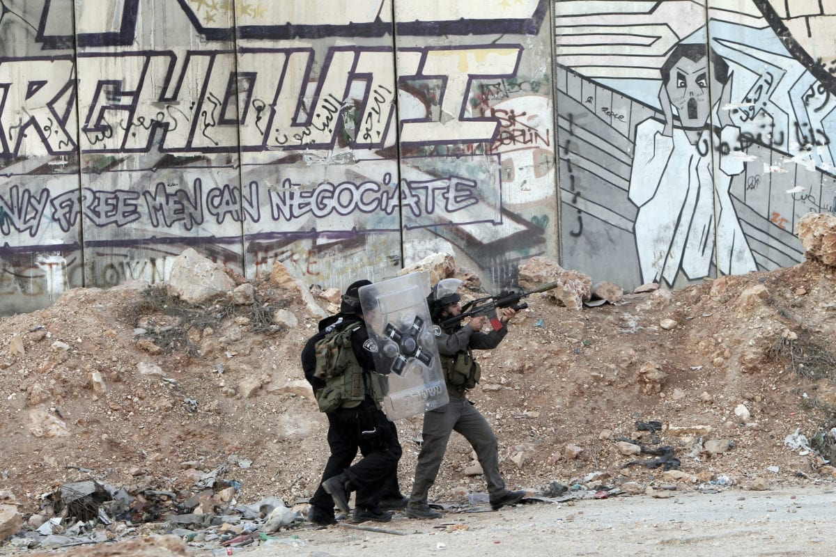 Israeli soldiers fire tear gas towards strone throwers demonstrating against the Israeli military offensive on the Gaza Strip at the Qalandia checkpoint, in the Israeli occupied West Bank, on November 18, 2012 [AHMAD GHARABLI/AFP/Getty Images]