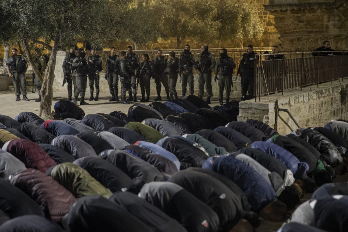 Palestinians perform prayer in front of Al-Rahma Gate (Gate of Mercy) of Al-Aqsa Mosque Compound, as Israeli security forces stand guard behind them after Al-Rahma Gate was chained by Israeli police in Jerusalem on February 20, 2019. [Faiz Abu Rmeleh - Anadolu Agency]