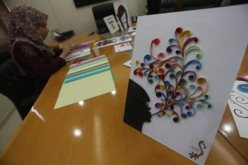 Gaza artist, Iman Al-Tayeb, cuts coloured paper into narrow strips and then curls and glues them to a board to make a 3D piece of art [Mohammed Asad/Middle East Monitor]
