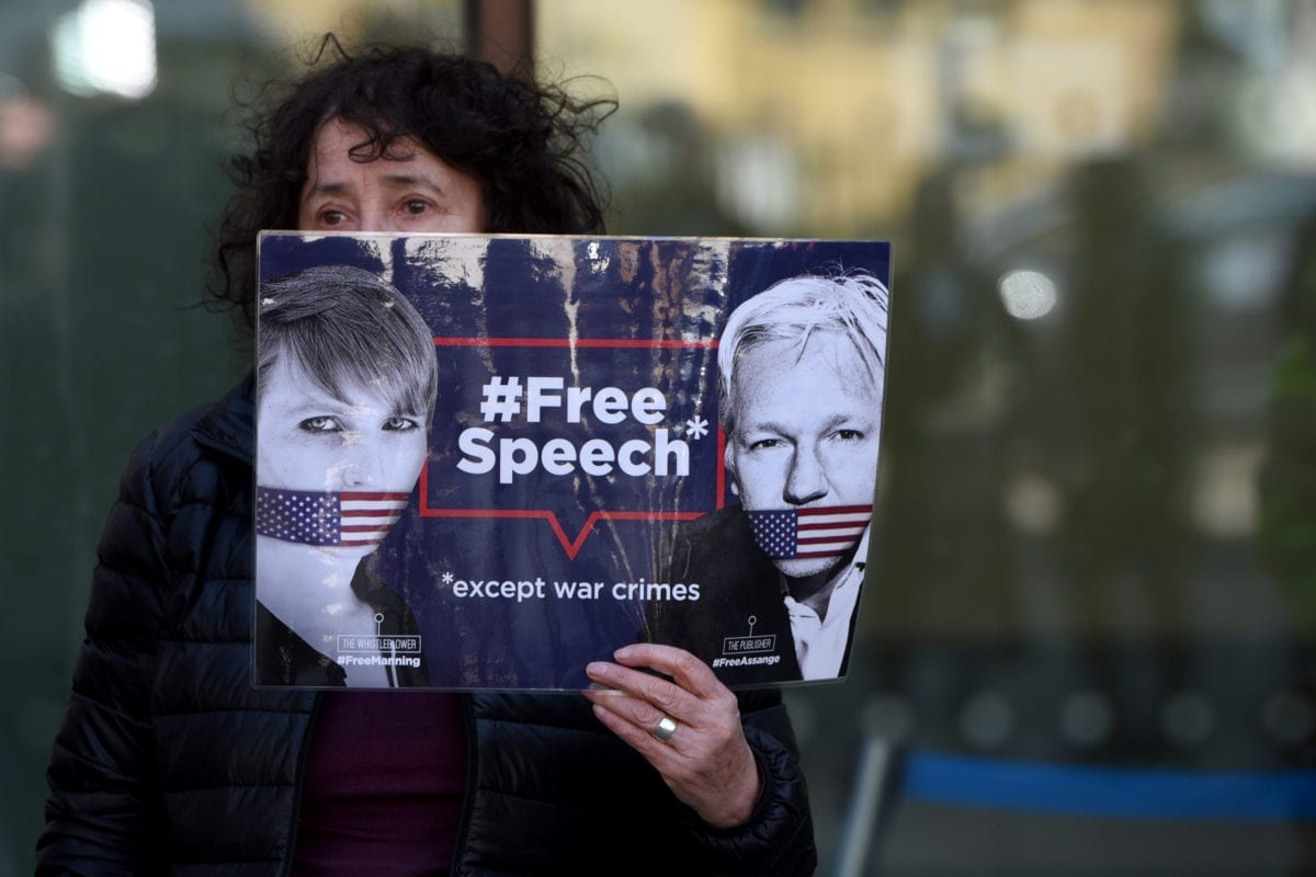 """A protester holds a banner reading """"Free Speech - Except War Crimes"""" during a protest outside Westminster Magistrates court, in London, United Kingdom on 11 April 2019. [Kate Green - Anadolu Agency]"""
