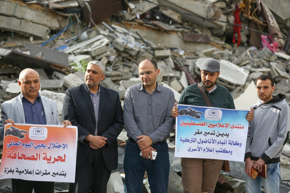 Journalists hold placards during a demonstration to protest Israeli attack towards Anadolu Agency's office after it was hit by Israeli warplanes' in Gaza 05, 2019. Israeli warplanes hit the building with at least 5 rockets after warning shots, Anadolu Agency's correspondent in Jerusalem reported. [Mustafa Hassona - Anadolu Agency]