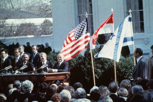 Egyptian President Anwar al-Sadat (L) US President Jimmy Carter and Israeli Premier Menachem Begin (R) laugh before sign of the Israel-Egypt Peace Agreement on 26 March, 1979 on the north lawn of the White House, Washington DC [AFP/Getty Images]