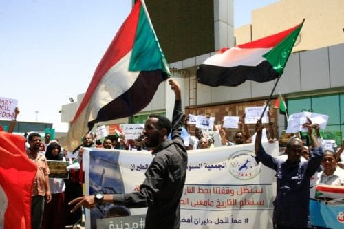 Sudanese aviation professionals wave national flags as they rally in support of civilian rule at Khartoum airport in the capital on 27 May, 2019 [Ebrahim Hamid/AFP/Getty]