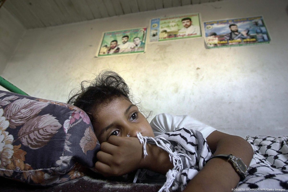 A Palestinian child rests in bed after she suffered shrapnel wounds to her shoulder and back after an Israeli forces fired a rocket in Gaza in 2003 [ROBERTO SCHMIDT/AFP/Getty Images]