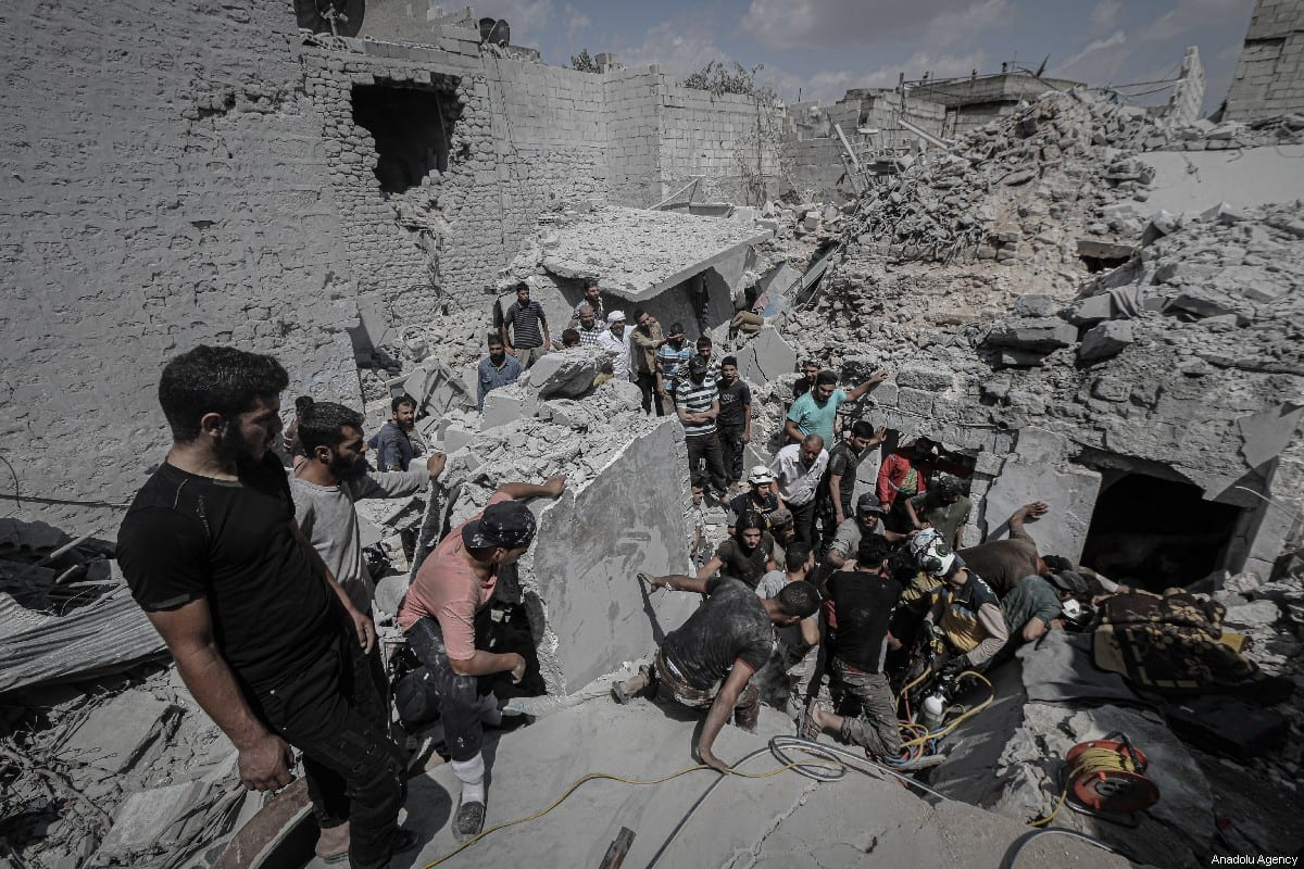 Civil defense crews and locals conduct search and rescue works amid debris after airstrikes of Assad Regime's warplanes hit the de-escalation zone of Ariha in Idlib, Syria on 12 July 2019. [Muhammed Said - Anadolu Agency]