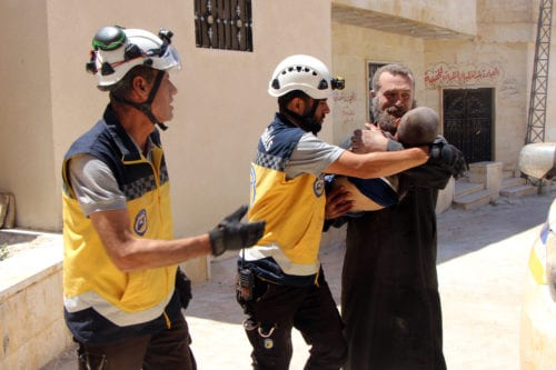 A dead body of a boy is being carried away by white helmet members a after Assad Regime's warplanes carried out airstrike over Kansafra town of Idlib de-escalation zone in Syria on 4 July 2019. [Syrian Civil Defense/ White Helmets / Handout - Anadolu Agency]