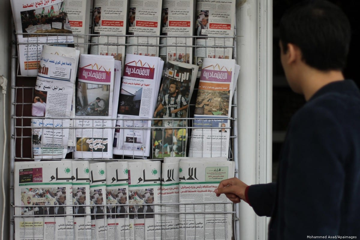 A Palestinian man waits at a newspaper stand in Gaza city, on 8 May 2014 [Mohammed Asad/Apaimages]