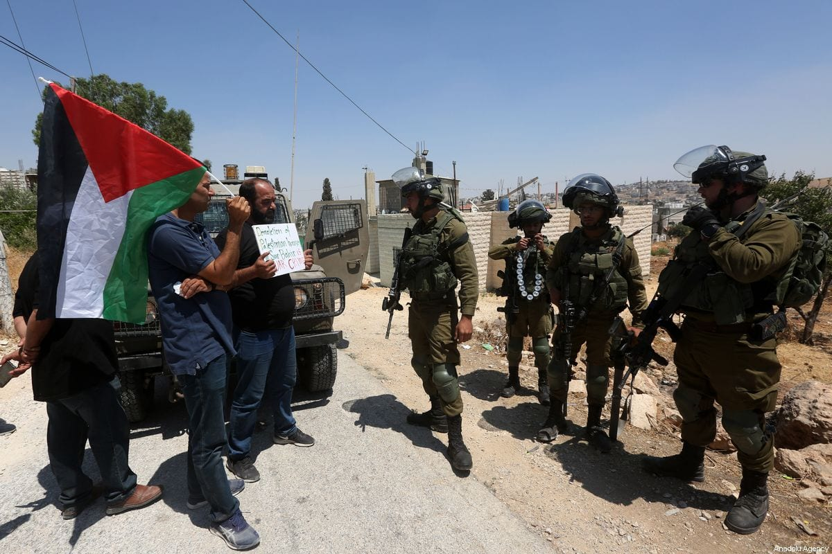 A man carries a Palestinian flag as a reaction to demolition of some of Palestinian houses by Israel in Sur Baher town on the southeastern outskirts of East Jerusalem on 2 August 2019. [Wisam Hashlamoun - Anadolu Agency]