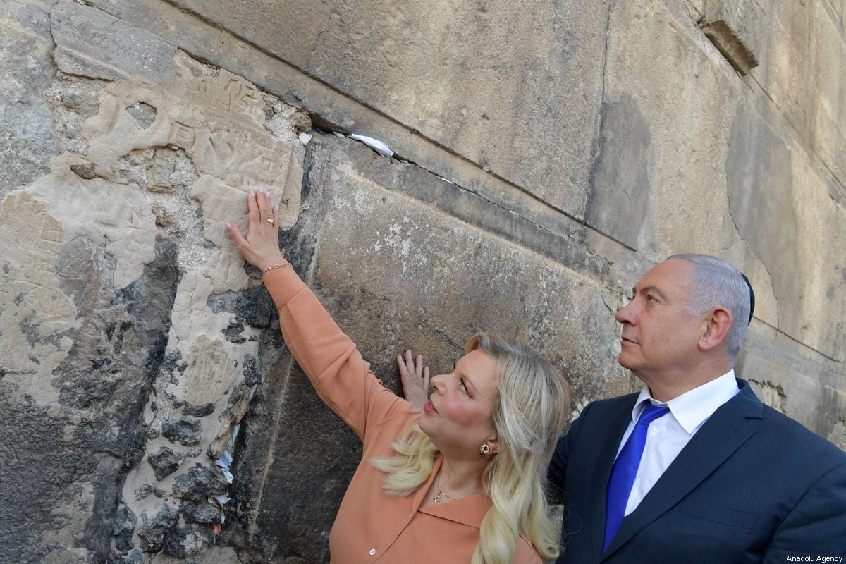 Israeli Prime Minister Benjamin Netanyahu (R) looks up while his wife Sara (L) touches the outside wall of the Ibrahimi Mosque in an event set to mark the 90th anniversary of a riot which took place in the city in 1929, in the West Bank town of Hebron, on 4 September 2019. [Kobi Gideon / GPO / Handout - Anadolu Agency]