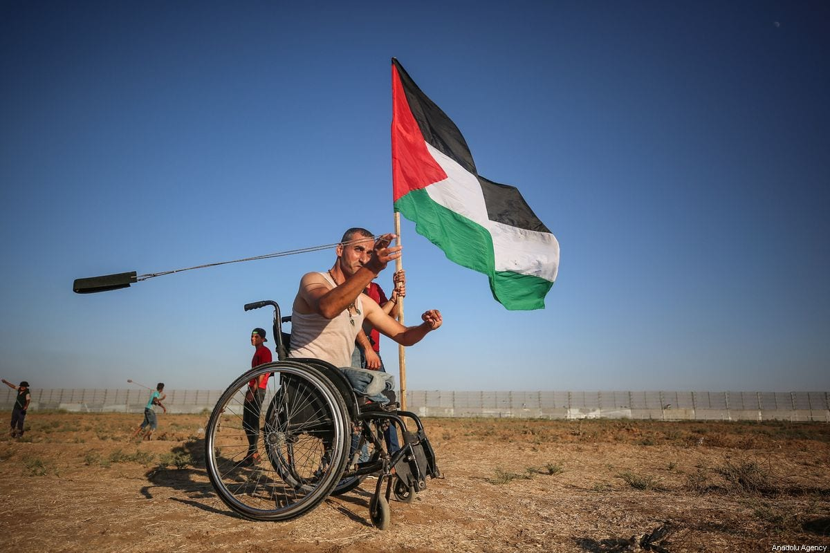 "A Palestinian disabled man throws a stone with a slingshot towards Israeli forces during ""Great March of Return"" demonstration at Israel-Gaza border, near Shuja'iyya neighborhood of Gaza City, Gaza on September 6, 2019 [Mustafa Hassona / Anadolu Agency]"