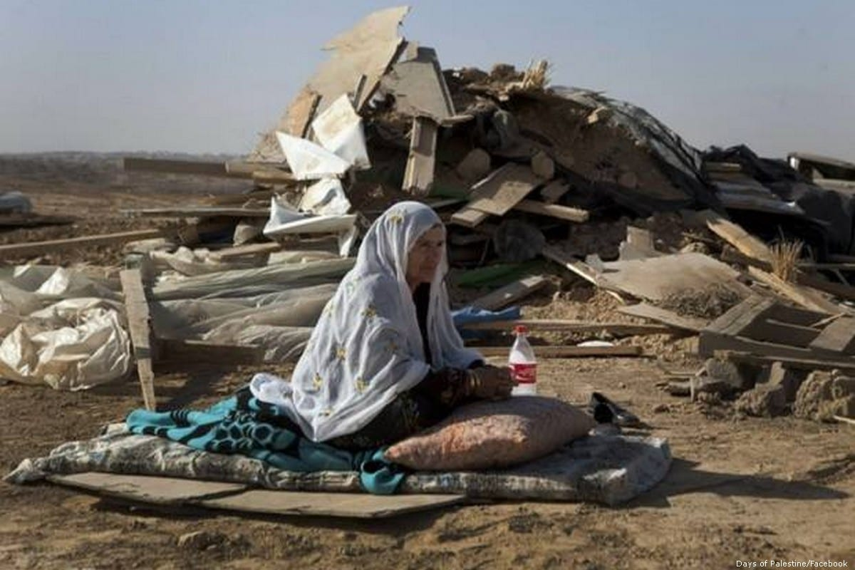 A Palestinian woman sits in front of her demolished home after Israeli forces ordered it for it be destroyed in the Negev on 15 February 2015 [Days of Palestine/Facebook]