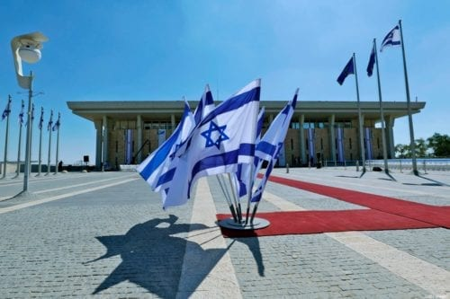 This picture taken on October 3, 2019 shows Israeli flags flying outside the Knesset (Israeli parliament) headquarters in Jerusalem [EMMANUEL DUNAND/AFP via Getty Images]
