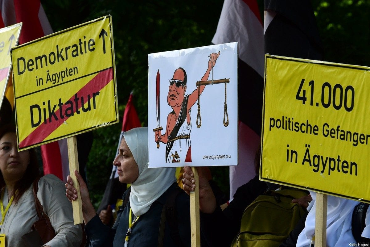 Protesters hold banners reading 'Democracy in Egypt- Dictatorship' ' 41 000 political prisoners in Egypt' prior arrival of Egyptian President Abdel Fattah al-Sisi for the meeting with German President in front of Schloss Bellevue castle on 3 June 2015 in Berlin. [JOHN MACDOUGALL/AFP via Getty Images]