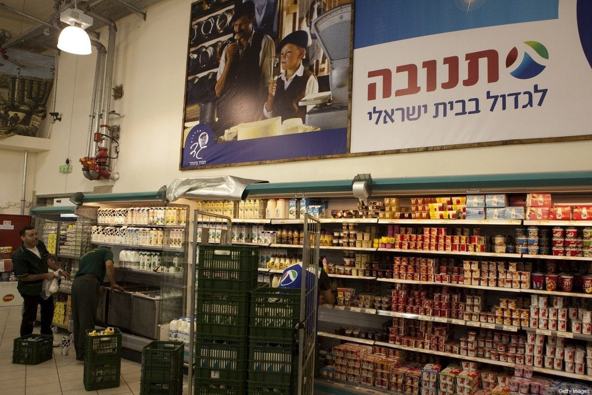 "TO GO WITH STORY BY PATRICK MOSER- Two Palestinians unload goods in a large Jewish owned supermarket located at the Gush Etzion junction in the Palestinian West Bank on July 4, 2010. Israeli settler and industrialist Avi Elkayam, 35, has no patience with the Palestinian boycott of settlement products. ""It's economic terrorism,"" he shouts shaking his fist. AFP PHOTO/MENAHEM KAHANA (Photo credit should read MENAHEM KAHANA/AFP via Getty Images)"