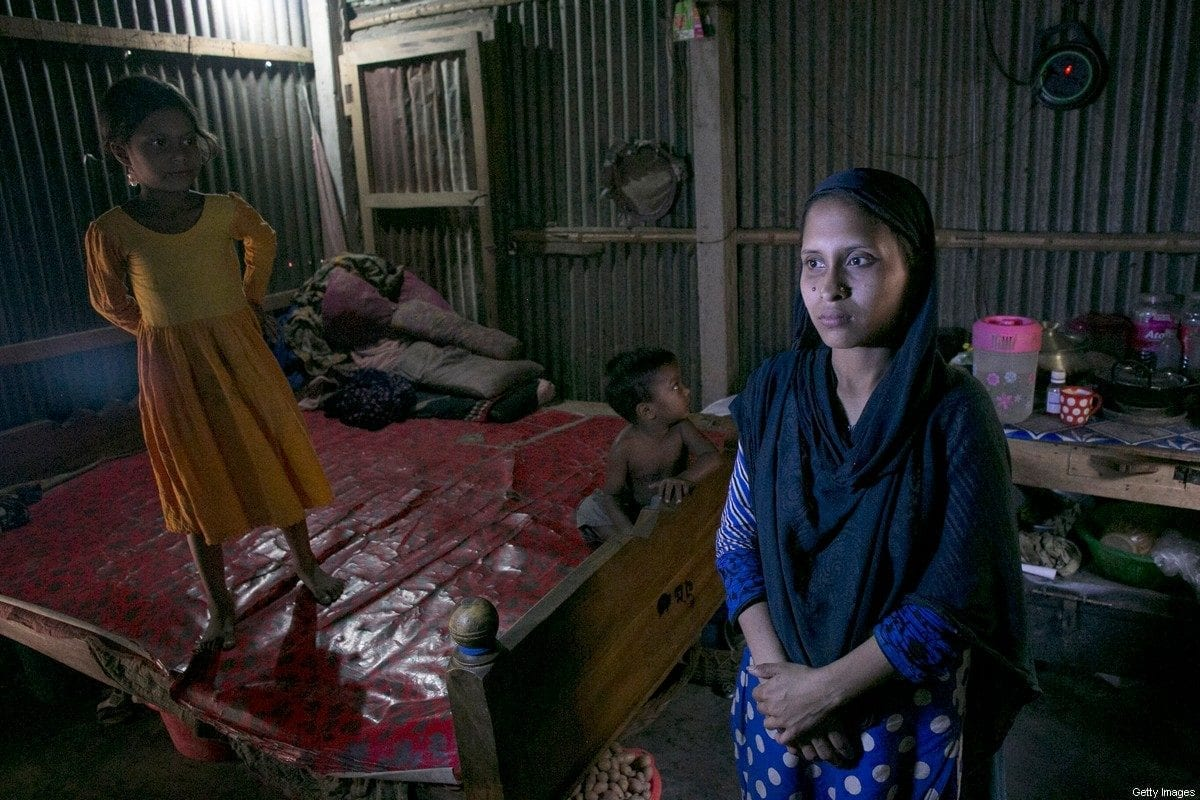 28 year old Reyhana Begum, who is preparing to work as a housekeeper in Saudi Arabia, poses for a photo in her home with her children March 14, 2016 in Dhaka, Bangladesh. Reyhana currently makes around 1,500-3,000 ($19.15-$38.30) taka per month working as a tailor, and her husband makes 5,000-6,000 ($63.83-$76.60) taka per month working as a rickshaw puller. She expects to earn 22,000 taka ($280.86) per month in Saudi Arabia, which she says she will put towards her daughters dowry and son's education. [Allison Joyce/Getty Images]