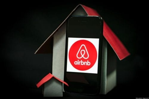 A phone screen displays logo of Airbnb with a house mock-ups next to it, on December 30, 2019 in Ankara, Turkey. [Metin Aktaş - Anadolu Agency]