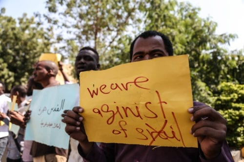 Protesters hold placards during a protest against meeting of Sudan's Sovereign Council Head Abdel-Fattah al-Burhan and Prime Minister of Israel Benjamin Netanyahu in Uganda, in front of Prime Ministry building in Khartoum, Sudan on 4 February, 2020 [Mahmoud Hajaj/Anadolu Agency]