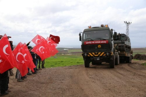 A photo taken from Turkey's Hatay province shows children greets soldiers with Turkish flags during Turkish military convoy consisting of howitzers, military vehicles and armored personnel carriers on the way towards observation points in Syria's Idlib, on 7 February, 2020 in Hatay, Turkey [Cem Genco/Anadolu Agency]