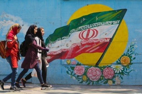 Young girls walk in front of a mural showing the Iranian national flag in the centre of the capital Tehran, on April 23, 2019 [ATTA KENARE / AFP via Getty Images]