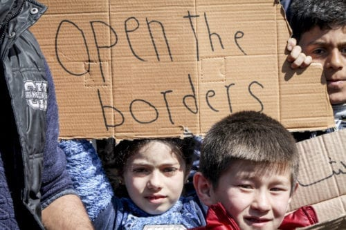 """Irregular migrants hold placards reading """"open the border gates"""" as they continue to wait in Edirne, Turkey to reach Greece on 3 March 2020 [Gökhan Zobar/Anadolu Agency]"""